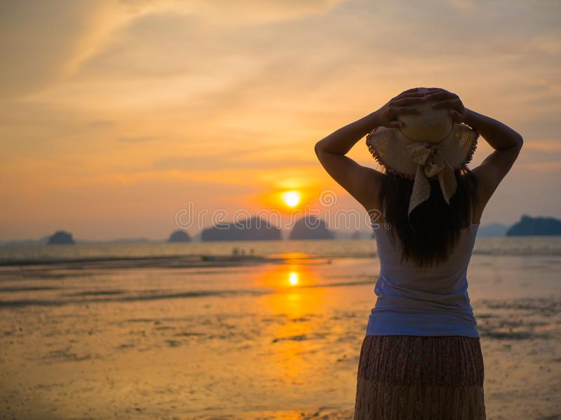 Woman wearing hat with open arms under the sunrise near the sea royalty free stock image