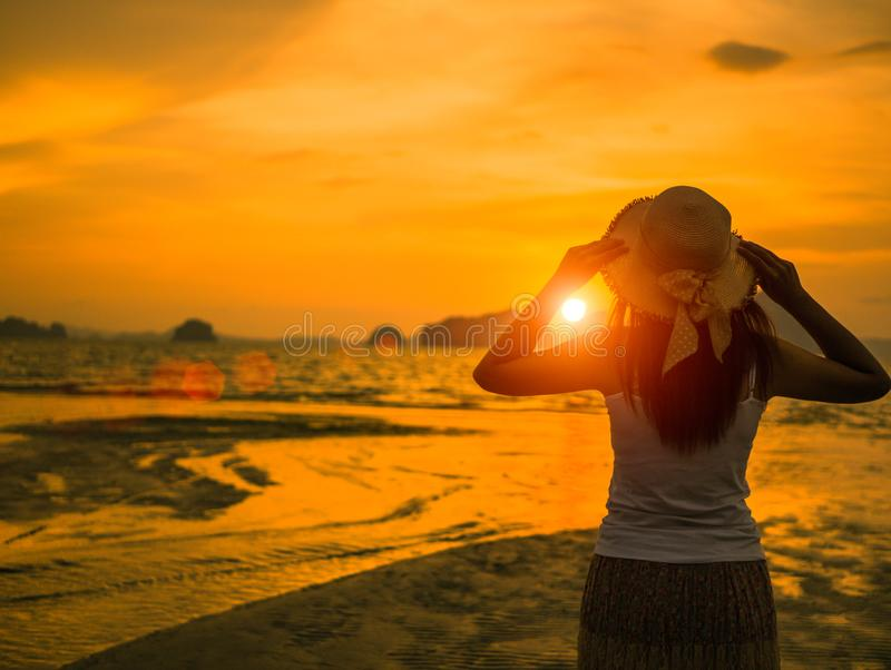 Woman wearing hat with open arms under the sunset near by the sea. Travel and holiday concept royalty free stock photo