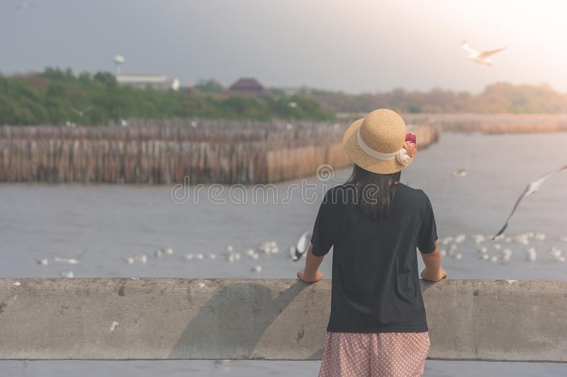 Woman wearing hat weave and standing on concrete bridge, she looking at sea and seagulls flying at Bangpu Recreation Center. stock photo