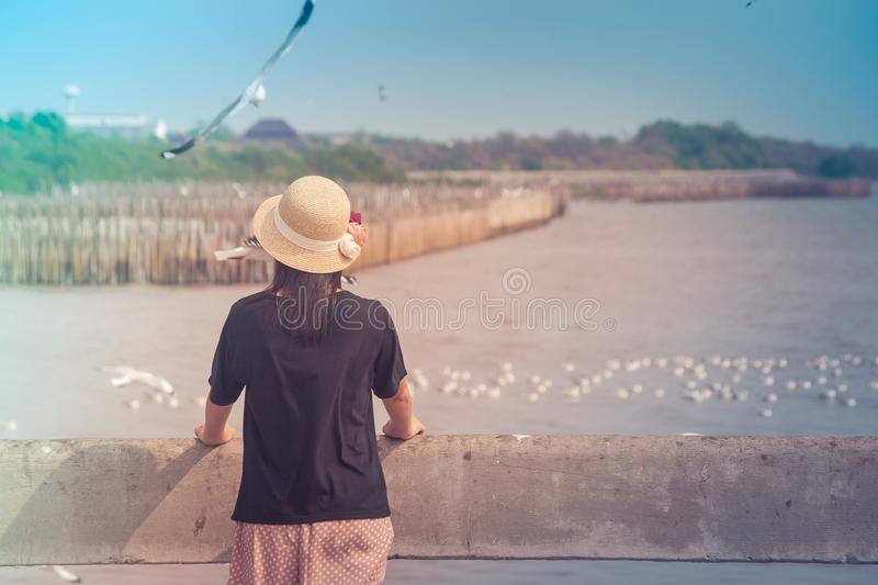 Woman wearing hat weave and standing on concrete bridge, she looking at sea and seagulls flying at Bangpu Recreation Center. stock image