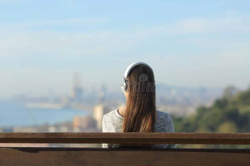 Woman wearing headphones listening to music on a bench. Back view of a woman wearing headphones listening to music sitting on a bench outdoors in city outskirts stock photo