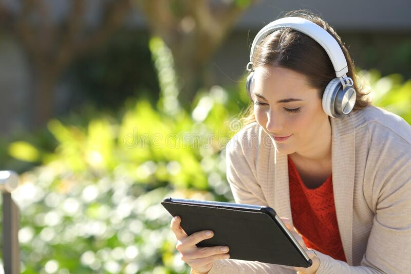 Woman wearing headphones watching media on tablet   in a park. Woman wearing headphones watching media or e-learning on tablet sitting in a park royalty free stock image