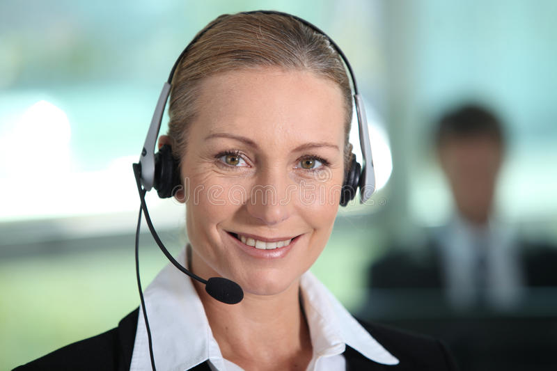 Woman wearing a headset. A woman smiling with headset stock photos