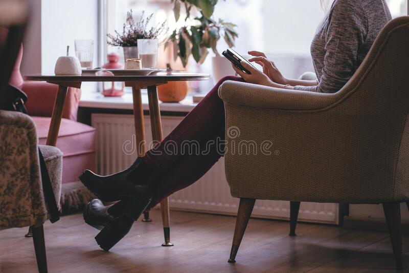 Woman Wearing Heather Gray Long Sleeve Top Red Fitted Pants and Chunky Boots Sitting on Sofa royalty free stock photo