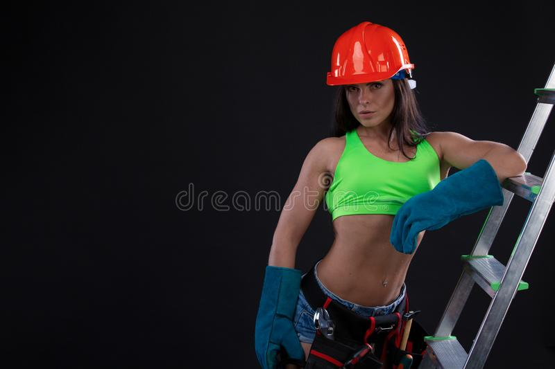 Woman wearing helmet, toolbelt standing on ladder. Girl working at flat remodeling royalty free stock photos