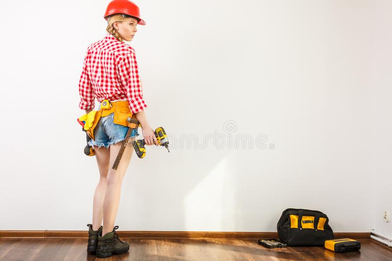 Woman wearing helmet, toolbelt about to drill wall royalty free stock photo