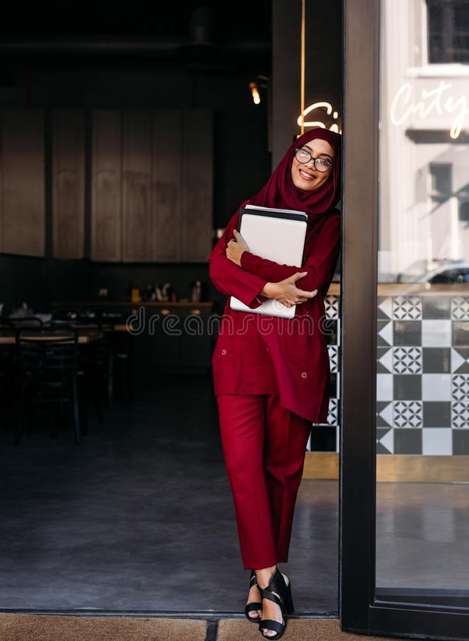 Muslim woman standing with laptop at coffee shop door stock photo