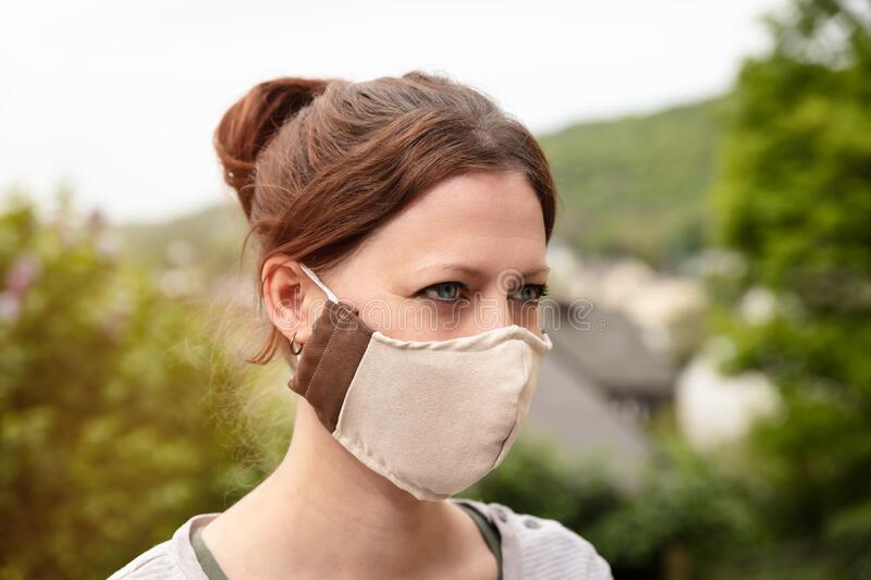 Woman is wearing a homemade fabric cloth face mask, coronavirus and covid-19 prevention and protection. Woman is wearing a homemade fabric cloth face mask stock photo