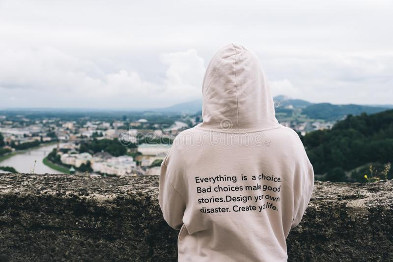 Woman wearing hoodie with inspirational quote against cityscape. Young woman wearing hoodie with inspirational quote against cityscape of Salzburg. Rear view royalty free stock image
