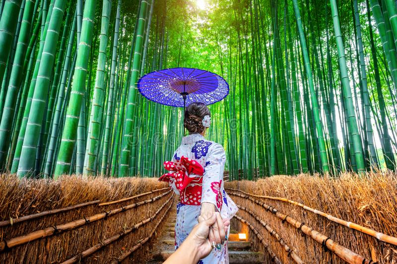 Woman wearing japanese traditional kimono holding man`s hand and leading him to Bamboo Forest in Kyoto, Japan.  stock photos