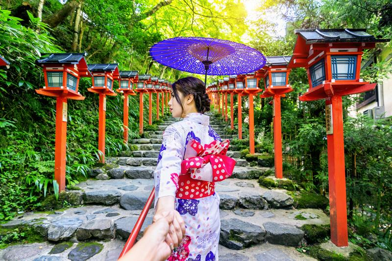 Woman wearing japanese traditional kimono holding man`s hand and leading him to Kifune shrine, Kyoto in Japan.  stock images