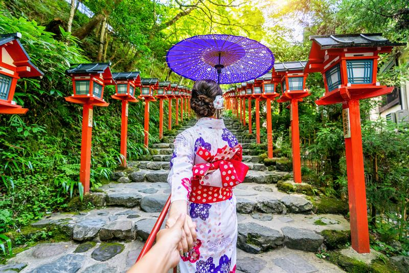 Woman wearing japanese traditional kimono holding man`s hand and leading him to Kifune shrine, Kyoto in Japan stock photos