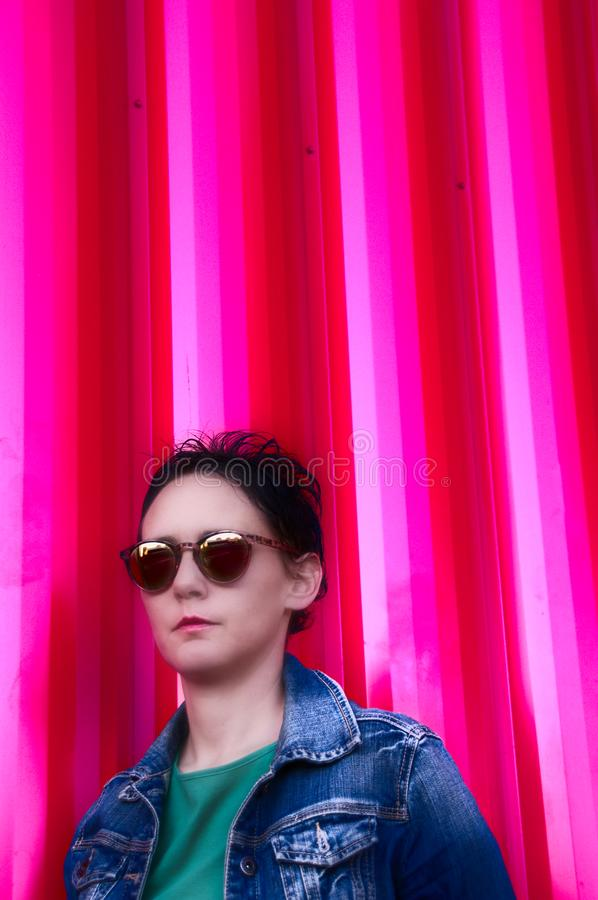 Woman wearing jean jacket and red background royalty free stock images