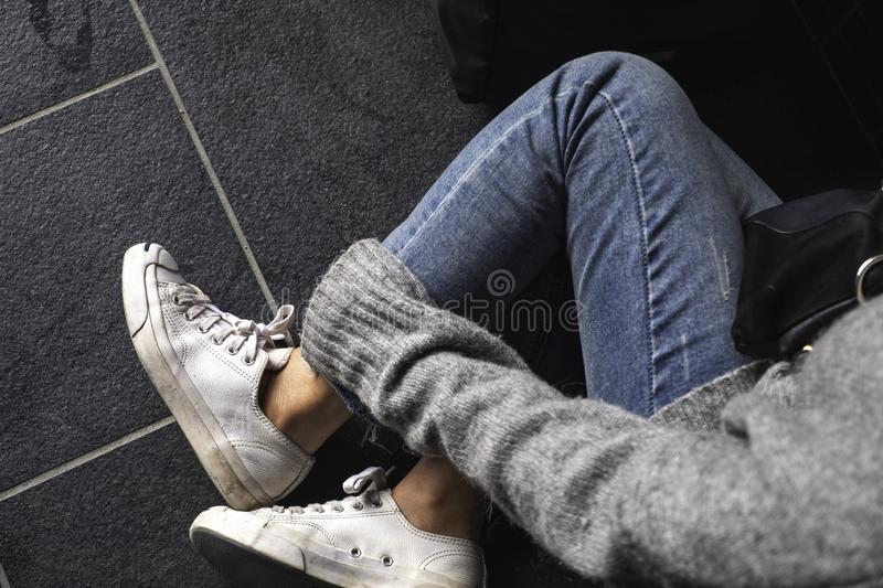 A woman wearing jean and white sneakers touching her leg while sitting on the floor royalty free stock images