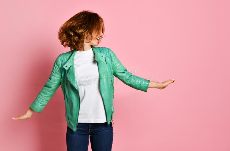 Woman wearing jeans and a jacket is shaking her head with her hair. The concept of joy, happiness, joy, fun royalty free stock photography