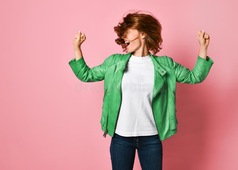 Woman wearing jeans and a jacket is shaking her head with her hair. The concept of joy, happiness, joy, fun stock photo