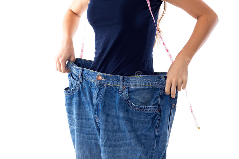 Woman wearing jeans of much bigger size. Woman in blue T-shirt with centimeter around her neck holding her jeans of much bigger size on white background in stock photography