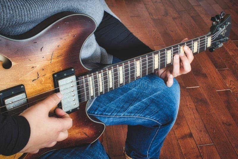 A woman playing an electric semi-hollow guitar stock photo