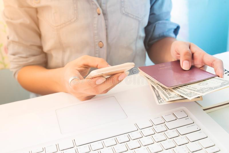Woman wearing jeans shirt using mobile phone and holding passport with dollar bills on hand, Business and Finance, Travel royalty free stock images