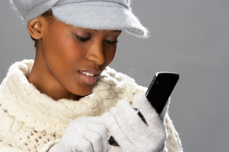 Woman Wearing Knitwear In Studio Using Mobile Royalty Free Stock Image