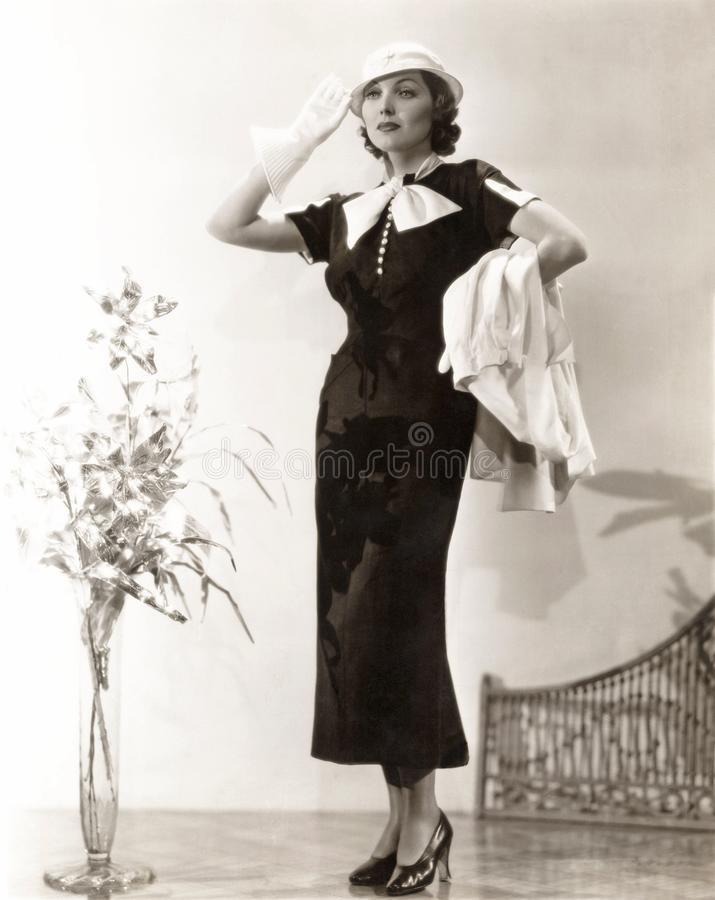 Woman wearing long dress with gauntlet gloves and matching hat royalty free stock images