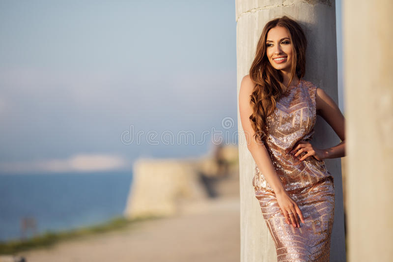 Woman is wearing luxury dress near antique column royalty free stock image