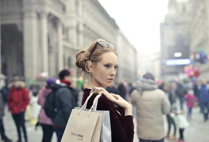 Woman Wearing Maroon Long-sleeved Top Carrying Brown and White Paper Bags in Selective Focus Photography stock image