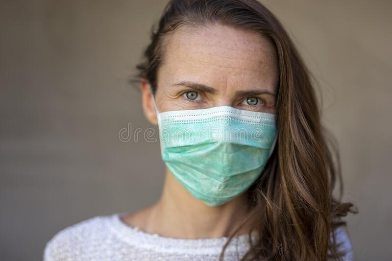Woman wearing mask as part of coronavirus prevention campaign. Woman wearing medical face protection mask; air pollution or allergies protection, coronavirus royalty free stock images