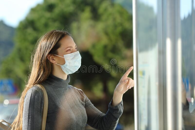 Woman wearing a mask checking schedule in a bus stop stock images