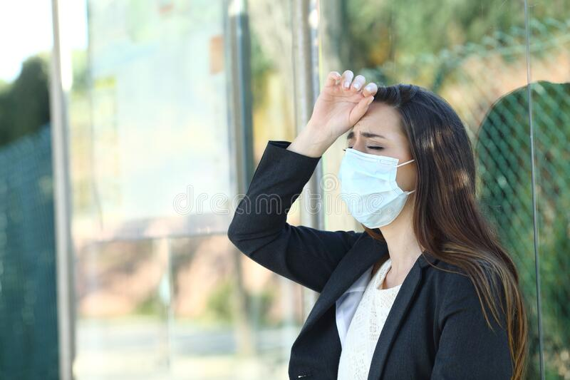 Woman wearing a mask complaining suffering head ache royalty free stock photography