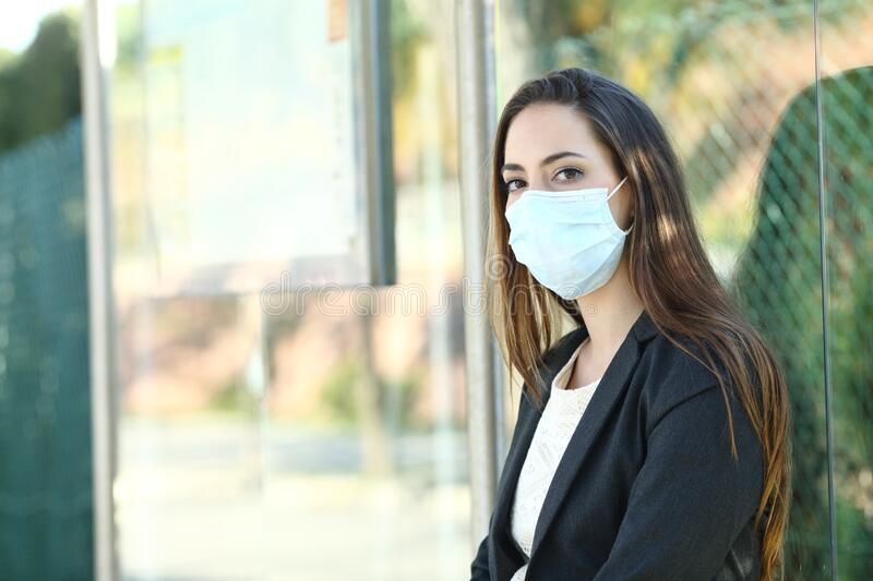 Woman wearing a mask to prevent contagion in a bus stop stock image