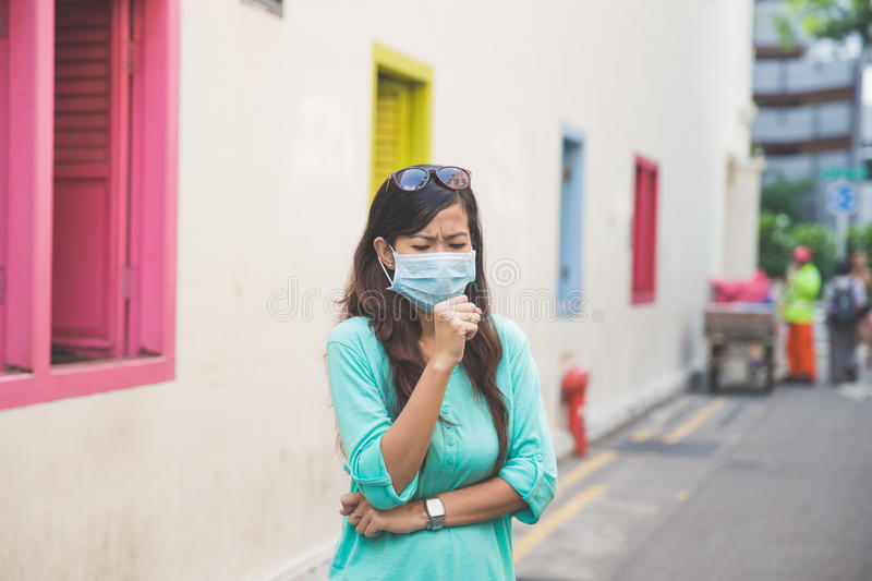 Woman wearing medical face mask in city royalty free stock images