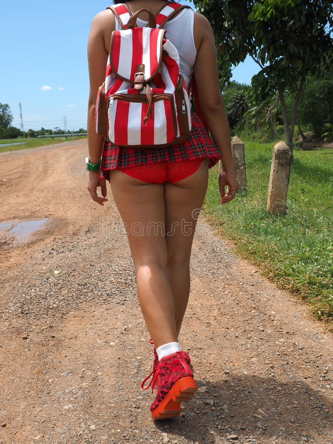 Woman wearing micro skirt and backpack walks outdoor. Woman wearing micro skirt walking on a dirt road stock images