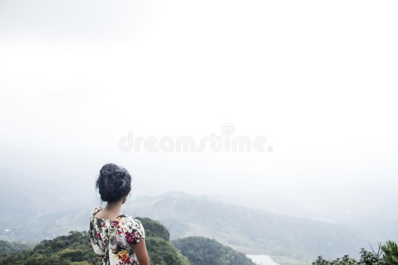 Woman Wearing Multicolored Floral Top Standing Near Mountain Under White Sky stock photos