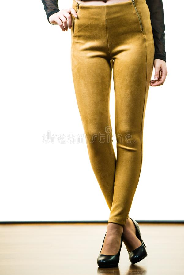 Woman wearing mustard tight pants. Unrecognizable woman wearing tight leggings pants mustard yellow brown well fitting skinny trousers royalty free stock photo