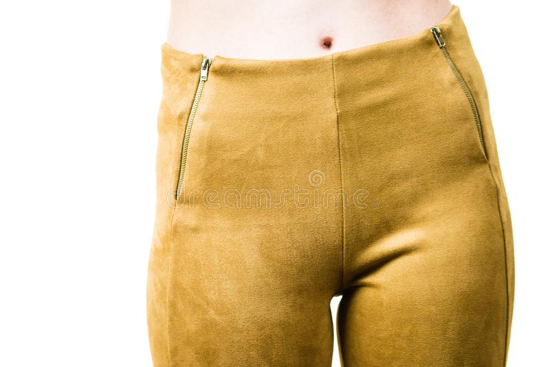 Woman wearing mustard tight pants. Unrecognizable woman wearing tight leggings pants mustard yellow brown well fitting skinny trousers stock photography