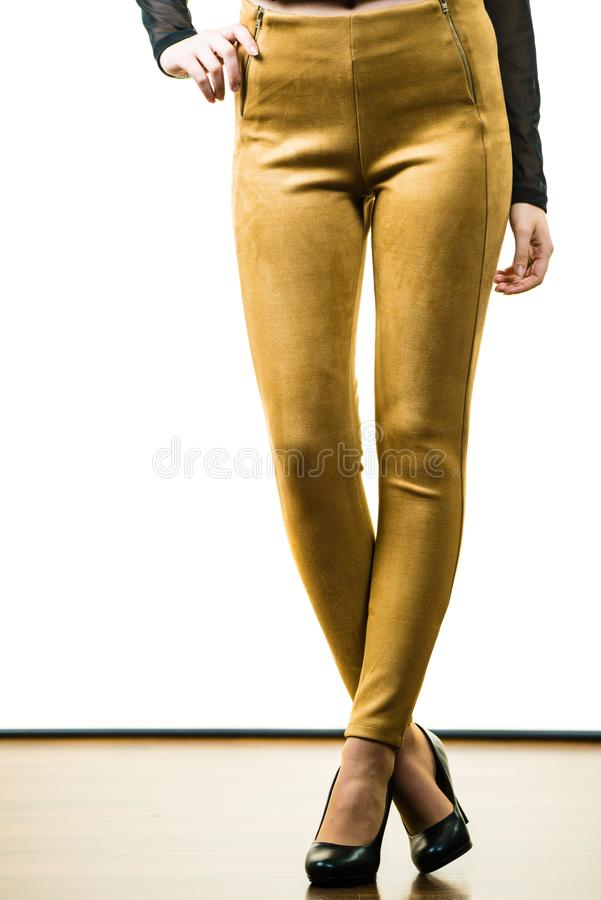 Woman wearing mustard tight pants. Unrecognizable woman wearing tight leggings pants mustard yellow brown well fitting skinny trousers royalty free stock image