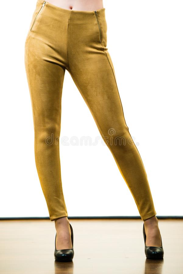 Woman wearing mustard tight pants. Unrecognizable woman wearing tight leggings pants mustard yellow brown well fitting skinny trousers stock image