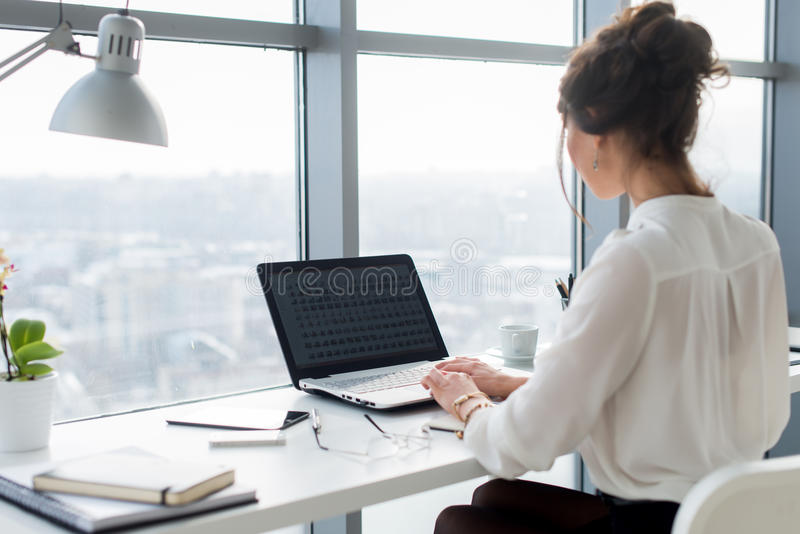 Woman wearing office suit sitting at her workplace, typing, searching new ideas for project. Female writer working with royalty free stock photos