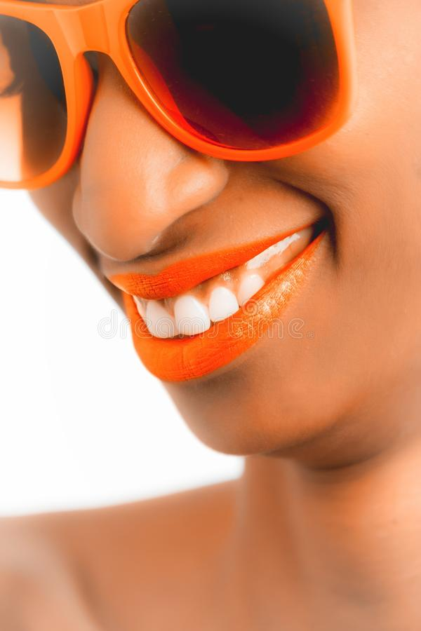 Woman Wearing Orange Frame Sunglasses and Orange Lipstick stock photo