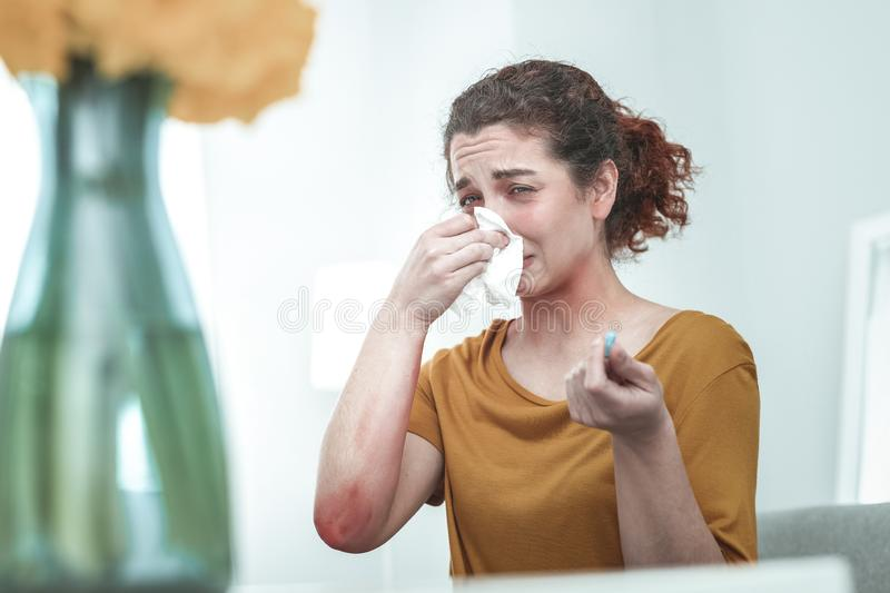 Woman wearing orange shirt drying nose suffering from allergy royalty free stock image