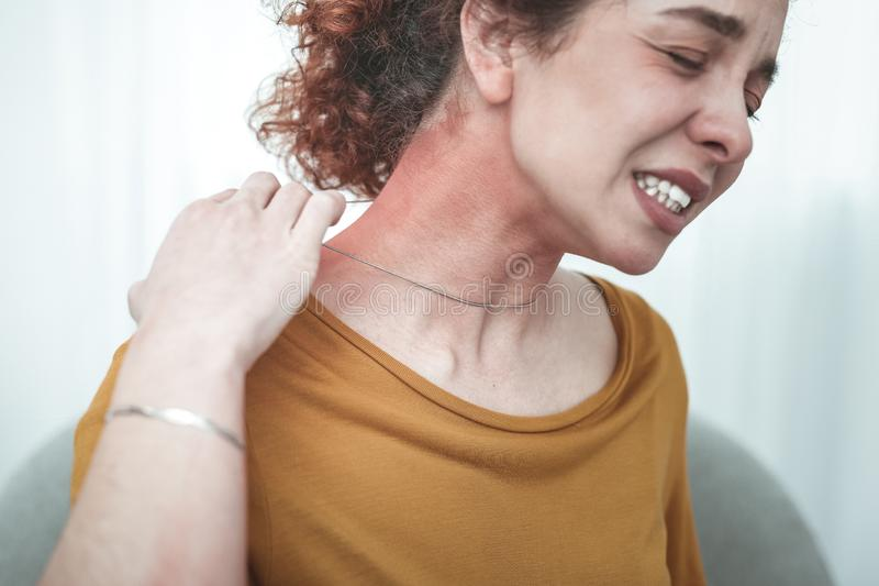 Woman wearing orange shirt having rash and reddening on neck stock photography