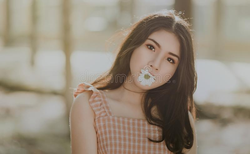 Woman Wearing Orange Sleeveless Dress Bites White Petaled Flower stock images