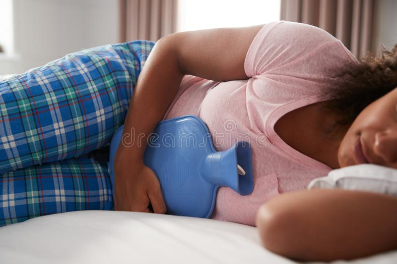 Woman Wearing Pajamas Suffering With Period Pain Lying In Bed With Hot Water Bottle stock photos