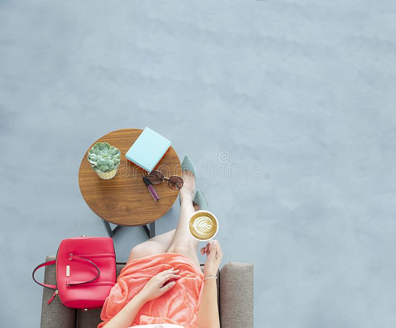 Woman Wearing Peach Skirt Sitting on Sofa Chair Holding a Cup of Coffee stock image