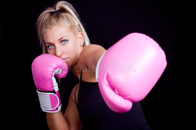 Woman wearing pink boxing gloves. Beautiful boxing girl wearing pink gloves - focus on face royalty free stock images