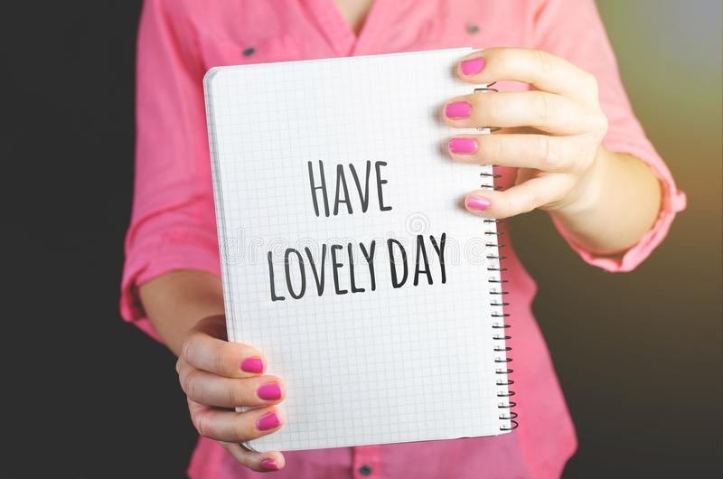 Woman Wearing Pink Dress Holding Graphing Notebook With Have a Lovely Day Sign royalty free stock image