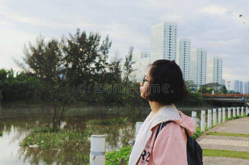 Woman Wearing Pink Hoodie Stand in Front of Body of Water stock image
