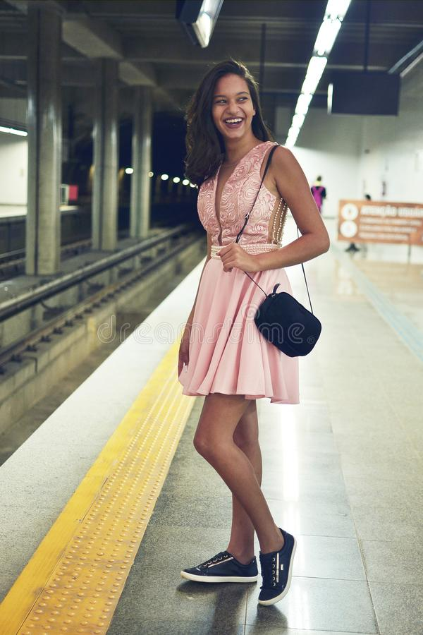 Woman Wearing Pink Plunging Necklace Midi Dress Standing on Train Station stock image