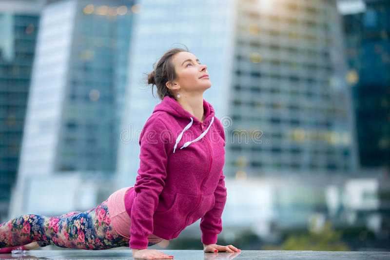 Woman wearing pink sportswear in upward facing dog pose. Young attractive woman practicing yoga, stretching in upward facing dog exercise, Urdhva mukha stock photos